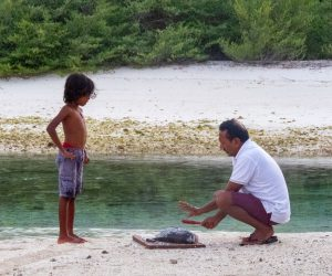 boy and grandfather cutting a fish on the beach